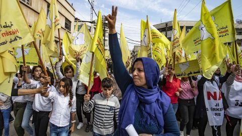 Syrian Kurds wave flags in Qamishli as they take part in a demonstration in support of the Syrian Democratic Forces on October 28.