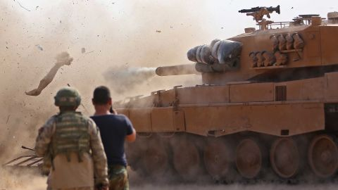 Turkish soldiers east of Ras al-Ain watch as a tank fires on positions held by the Syrian Democratic Forces on Monday, October 28.