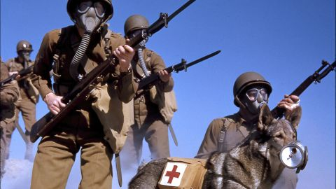 1943: A group of US Army soldiers, rifles in hand, wear a gas masks during a training exercise related to chemical attacks in California. Along with the soldiers, a dog with a first aid pack strapped to it wears a special muzzle filter to protect it from gas.