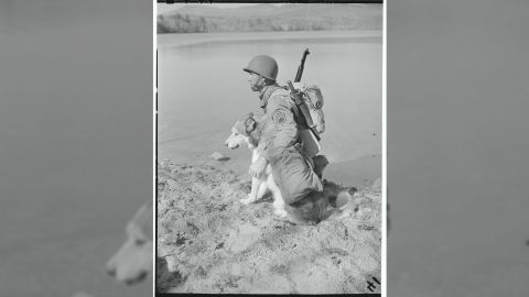 """1940: Sgt. Stanley Novak rests at a lakeside with """"Mukluk"""" during the training routine on Lake Chiquora."""