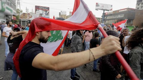 A Lebanese protester uses a national flag to protect himself from the rain on October 23, 2019, in the area of Zouk Mosbeh north of the capital Beirut. - Tens of thousands of Lebanese protesters kept the country on lockdown, rallying for a sixth consecutive day to demand new leaders despite the government's adoption of an emergency economic rescue plan. Demonstrations initially sparked by a proposed tax on WhatsApp and other messaging apps quickly grew into an unprecedented cross-sectarian street mobilisation against the political class. (Photo by JOSEPH EID / AFP) (Photo by JOSEPH EID/AFP via Getty Images)