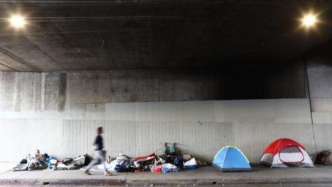 A man walks past a homeless encampment beneath an overpass in Los Angeles, California.