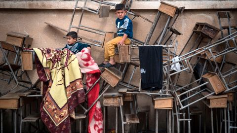 Displaced Syrian children sit on classroom tables at a school turned into a shelter on Thursday, October 24.