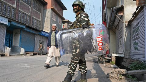 TOPSHOT - A resident walks past Indian paramilitary troopers standing guard during a lockdown in Srinagar on October 29, 2019. - Nearly 30 Euro MPs, drawn mainly from extreme right-wing parties, are on October 29 becoming the first international delegation to visit Indian Kashmir since authorities imposed a security clampdown in August to back the ending of the region's autonomy. (Photo by Tauseef MUSTAFA / AFP) (Photo by TAUSEEF MUSTAFA/AFP via Getty Images)