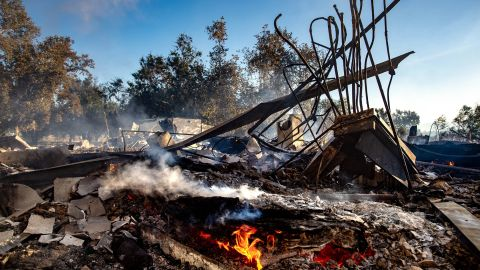 The remains of the Louis Robidoux Nature Center keep smoldering after the structure was destroyed by a wildfire in Riverside, California.