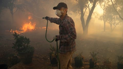 Marco Alcaraz uses a garden hose to try to slow down the advance of the Easy Fire in Simi Valley.