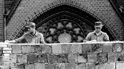 East German workers embed broken glass in the top of the Berlin Wall on August 22, 1961, shortly after construction began.