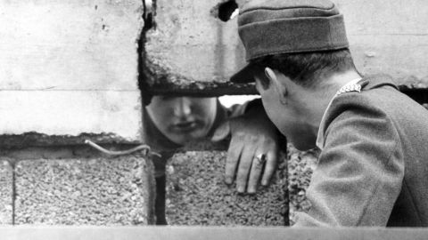 A guard from West Berlin (right) talks to an East Berliner through a hole in the Wall, September 1962.