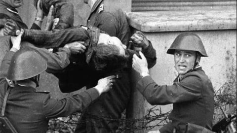 """East German bricklayer Peter Fechter, 18, is carried away by border guards after being shot and fatally wounded while attempting to flee to the West in August, 1962. <a href=""""https://www.britannica.com/topic/Berlin-Wall"""" target=""""_blank"""" target=""""_blank"""">Almost 200 </a>people were killed attempting to cross the Wall between 1961 and 1989."""