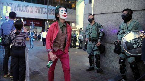A man dressed as the Joker for Halloween walks past police officers on October 31.