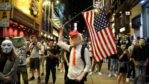 """A person dressed as President Donald Trump waves an American flag on a street in Hong Kong on Thursday, October 31, 2019. Hong Kong authorities braced as pro-democracy protesters urged people on Thursday to celebrate Halloween by wearing masks on a march in defiance of a <a href=""""https://www.cnn.com/2019/10/30/asia/halloween-hong-kong-mask-ban-intl-hnk/index.html"""" target=""""_blank"""">government ban on face coverings</a>."""