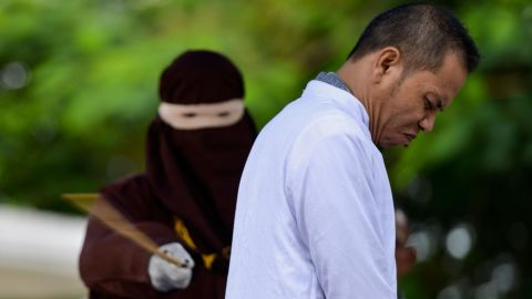 Aceh Ulema Council (MPU) member Mukhlis reacts as he is whipped in public by a member of the Sharia police in Banda Aceh on October 31, 2019. - An Indonesian man working for an organisation which helped draft strict religious laws ordering adulterers to be flogged was himself publically whipped on October 31 after he was caught having an affair with a married woman. (Photo by CHAIDEER MAHYUDDIN / AFP) (Photo by CHAIDEER MAHYUDDIN/AFP via Getty Images)