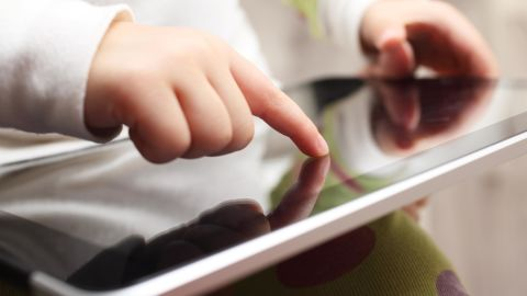 Close-up of a child playing on a touch screen tablet.
