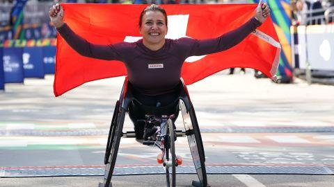 Manuela Schar holds the Swiss flag aloft after winning a third-straight NYC Marathon.