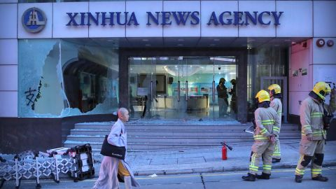 Firefighters stand outside the offices of China's Xinhua News Agency after its windows were damaged by protesters in Hong Kong on Saturday, November 2. Hong Kong riot police fired multiple rounds of tear gas and used a water cannon Saturday to break up a rally by thousands of masked protesters demanding autonomy after Beijing indicated it could tighten its grip on the Chinese territory.