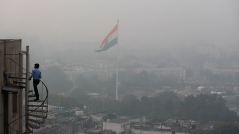 An Indian walks up to the stairs as Delhi's sky line is seen enveloped in smog and dust in New Delhi, India, Friday, Nov. 1, 2019. An expert panel in India's capital has declared a health emergency due to air pollution choking the city, with authorities ordering schools closed until Nov. 5. (AP Photo/Manish Swarup)