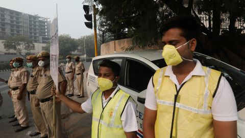 """Volunteers and police wearing masks hold a banner urging drivers to obey the """"odd-even"""" scheme."""
