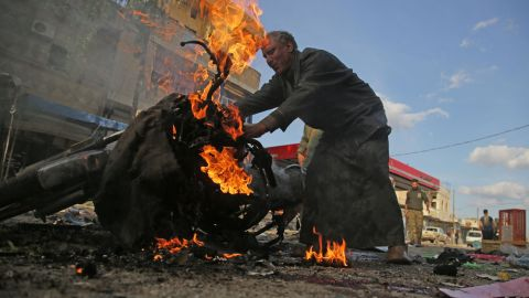"""A man stands next to a burning motorcycle at the site of <a href=""""https://www.cnn.com/2019/11/02/middleeast/tal-abyad-syria-car-bomb-explosion/index.html"""" target=""""_blank"""">a deadly car bomb explosion</a> in Tal Abyad, Syria, on Saturday, November 2. Turkey's defense ministry blamed the Kurdish People's Protection Units and the Kurdistan Workers Party, while a group aligned with the Kurds blamed Turkey."""
