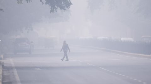 """A man crosses a street in smoggy conditions in New Delhi on November 4, 2019. - Millions of people in India's capital started the week on November 4 choking through """"eye-burning"""" smog, with schools closed, cars taken off the road and construction halted. (Photo by Jewel SAMAD / AFP) (Photo by JEWEL SAMAD/AFP via Getty Images)"""