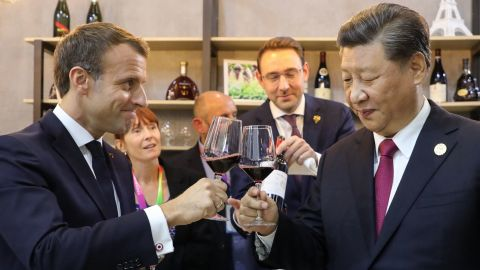 China's President Xi Jinping (R) and French President Emmanuel Macron (L) taste wine as they visit France's pavilion during the China International Import Expo in Shanghai on November 5.