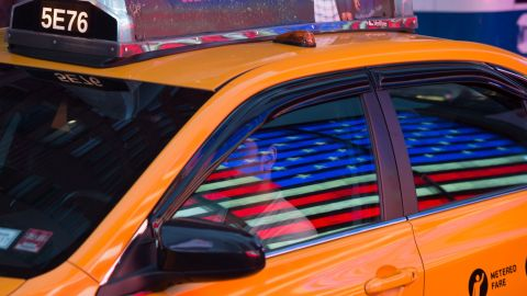 The American flag is reflected on a taxi cab in Times Square on Memorial Day, May 30, 2016 in New York. / AFP / Bryan R. Smith        (Photo credit should read BRYAN R. SMITH/AFP via Getty Images)