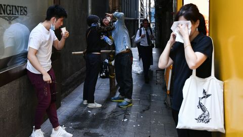People react after tear gas was fired by police during a protest in Hong Kong's Central District on November 11.