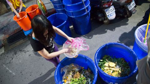 TAIPEI, TAIWAN - 2016/05/02: Residents of a Taipei community sort food waste into large blue containers for disposal by the city garbage collectors. Different trucks are used for garbage, recyclables and food waste. Since the government initiated the garbage sorting program in the late 1990's, Taipei's recycling rate has grown to 67%.. (Photo by Craig Ferguson/LightRocket via Getty Images)