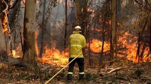 A National Parks and Wildlife crew member fights flames in New South Wales on Tuesday.