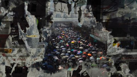 Marching anti-government protesters are seen through a window with peeled-off posters on October 1.Vincent Yu/AP