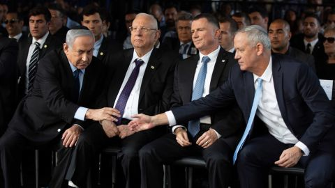 """Netanyahu and Israeli Blue and White party chief Benny Gantz reach to shake hands during a state memorial ceremony for former Israeli Prime Minister Yitzhak Rabin and his wife Leah in Jerusalem on November 10. Exit polls for a <a href=""""https://edition.cnn.com/2019/09/18/middleeast/israel-elections-gantz-netanyahu-results-intl/index.html"""" target=""""_blank"""">repeat general election in September</a> failed to give either of the political rivals a majority in the new parliament."""