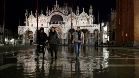 People walk across the partially flooded St. Mark's square in the lagoon city of Venice, Italy, November 14, 2019. REUTERS/Flavio Lo Scalzo