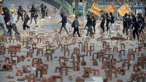 Protesters walk past barricades of bricks on a road near the Hong Kong Polytechnic University on November 14.