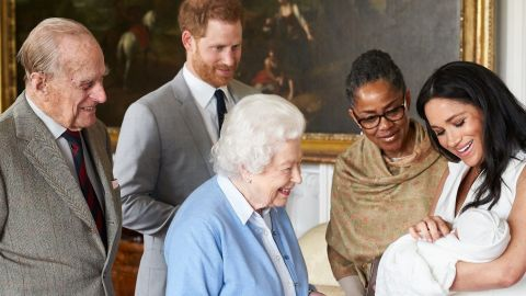 """The Queen looks at <a href=""""http://www.cnn.com/2019/05/08/uk/gallery/archie-royal-baby-harry-meghan/index.html"""" target=""""_blank"""">her new great-grandchild, Archie,</a> in May 2019. Archie is the first child of Prince Harry, second from left, and his wife Meghan, the Duchess of Sussex. Prince Philip is on the far left. Meghan's mother, Doria Ragland, is next to her at right."""