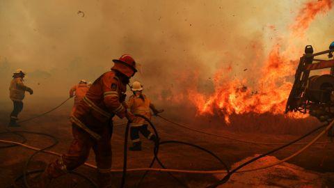 Firefighters battle a fire on November 13, 2019 in Hillville, Australia.