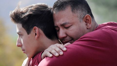 Marco Reynoso hugs his son, 11th-grader Dylan Reynoso, after reuniting at a park near Saugus High School after a shooting at the school killed two students and injured three.