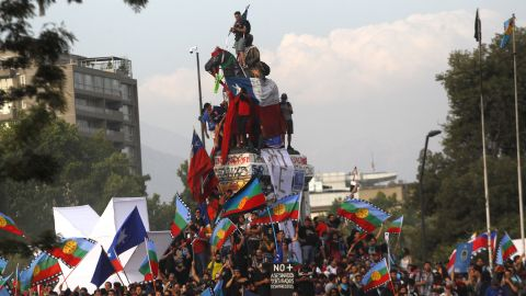 Demonstrators climb on top of a monument in Plaza Italia, Santiago during a protest against Chilean President Sebastian Pinera on November 14, 2019.
