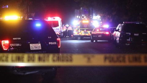 Police and emergency vehicles work at the scene of a shooting at a backyard party, Sunday, Nov. 17, 2019, in southeast Fresno, Calif. Multiple people were shot and at least four of them were killed Sunday at a party in Fresno when suspects sneaked into the backyard and fired into the crowd, police said. (Larry Valenzuela/The Fresno Bee via AP)