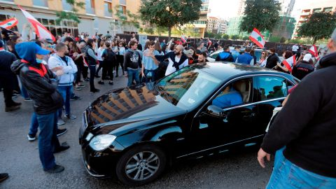Lebanese protesters block the road before a vehicle in Beirut's downtown district near the country's parliament on November 19, 2019.
