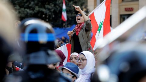 A Lebanese protester holds a national flag as she chants during a demonstration at Riad al-Solh square, Beirut, on Tuesday.