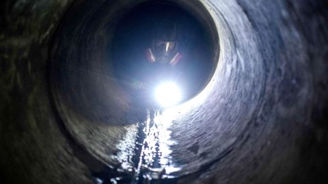 A protester uses a flashlight while crawling through a sewer tunnel to see how wide it is as he and others try to find an escape route from the Hong Kong Polytechnic University on November 19.