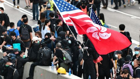 A man waves a US and Hong Kong flag while standing on a divider after he and other protesters occupied Harcourt Road while marching against a controversial extradition bill in Hong Kong on July 21, 2019. - Another huge anti-government march kicked off in Hong Kong on July 21 afternoon with seemingly no end in sight to the turmoil engulfing the finance hub, sparked by years of rising anger over Beijing's rule. (Photo by Anthony WALLACE / AFP)        (Photo credit should read ANTHONY WALLACE/AFP via Getty Images)