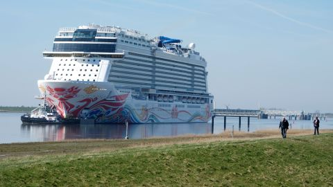 Spectators watch as the Norwegian Joy cruise ship makes its way down the Ems River near Emden in northern Germany on March 27, 2017.