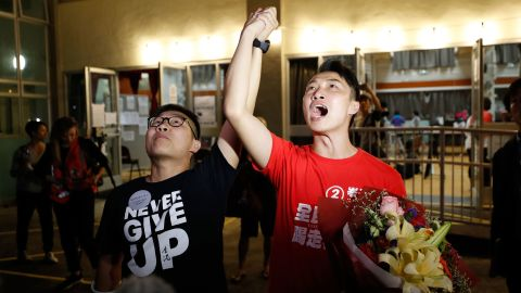"""Pro-democracy candidate Jimmy Sham, right, celebrates with a supporter after winning his election in the Sha Tin district, early November 25. """"Today's result represents (my constituency's) support to protesters. The government should immediately establish the Five Demands and respond to the public's voices,"""" Sham posted on Facebook, referencing a long-standing protest slogan."""