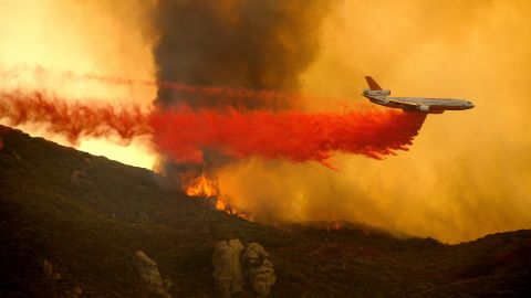 A DC-10 air tanker drops retardant to slow the Cave Fire.