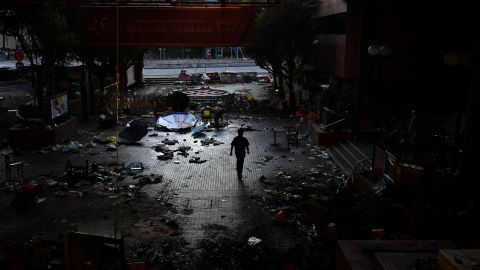A man walks past debris littering the entrance at the Hong Kong Polytechnic University campus in the Hung Hom district of Hong Kong on November 27, 2019, over a week after police surrounded the building while protesters were still barricaded inside. - Teams at one of Hong Kong's top universities picked through the chaotic aftermath of a violent occupation by protesters for a second day on November 27 as the school searches for elusive holdouts -- and a way forward for a devastated institution. (Photo by Anthony WALLACE / AFP) (Photo by ANTHONY WALLACE/AFP via Getty Images)