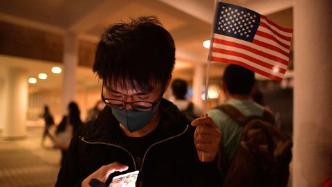 A pro-democracy protester holds up a US national flag while checking his phone during a gathering of thanks at Edinburgh Place in Hong Kong's Central district on November 28, 2019, after US President Donald Trump signed legislation requiring an annual review of freedoms in Hong Kong. - China on November 28 threatened to retaliate after US President Donald Trump signed legislation supporting Hong Kong pro-democracy protesters, just as the world's top two economies edge towards a trade truce. (Photo by Nicolas ASFOURI / AFP) (Photo by NICOLAS ASFOURI/AFP via Getty Images)