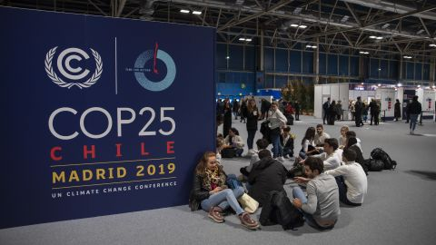 People sit on the ground during the opening day of the COP25 climate conference in Madrid, Spain.