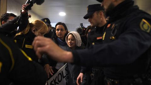 Thunberg is escorted by police on her arrival at Atocha train station in Madrid.