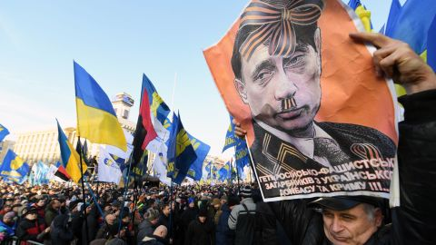 """TOPSHOT - An activist holds a poster depicting Russian President Vladimir Putin as people gather for a mass rally called """"Red lines for ZE"""" (Ukrainian President's nickname) to demand """"no capitulation"""" to Russia, at the Independence Square in Kiev, on December 8, 2019, ahead of a summit in Paris aimed at ending the hostilities between Ukraine and Russia. - France's President, Germany's Chancellor, Ukraine's President and Russia's President will take part in a December 9 summit in Paris, moderated by the leaders of France and Germany, aimed at ending more than five years of fighting between the two countries. (Photo by Sergei SUPINSKY / AFP) (Photo by SERGEI SUPINSKY/AFP via Getty Images)"""