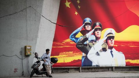 A man waits beside his electric scooter as he charges it next to a Chinese military recruitment poster in Shanghai on  July 29, 2015. AFP PHOTO / JOHANNES EISELE        (Photo credit should read JOHANNES EISELE/AFP via Getty Images)